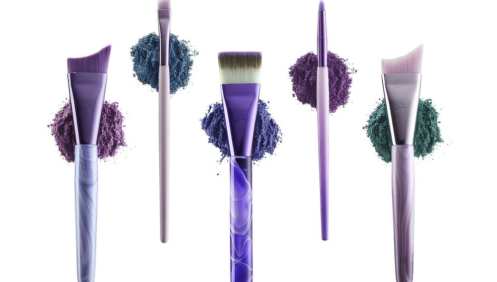 """Five cosmetic brushes from Anisa Internationals """"Spiral Fusion"""" brush set, each brush set upon it's own loose pile of cosmetic powders."""